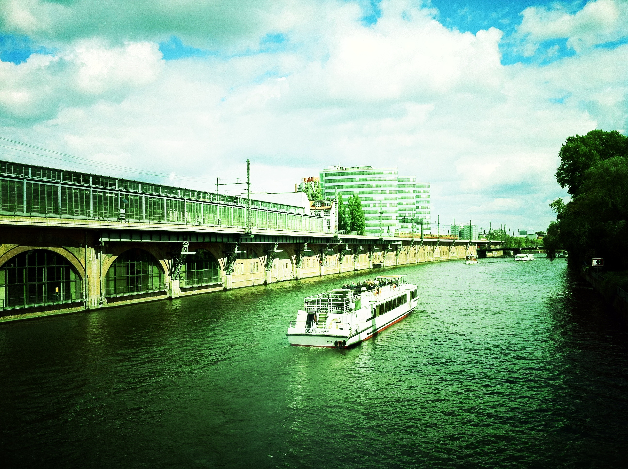 A photograph of a boat going down a river in Berlin.